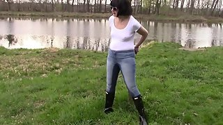 Pee in jeans and handcuffs on the bank of a pond